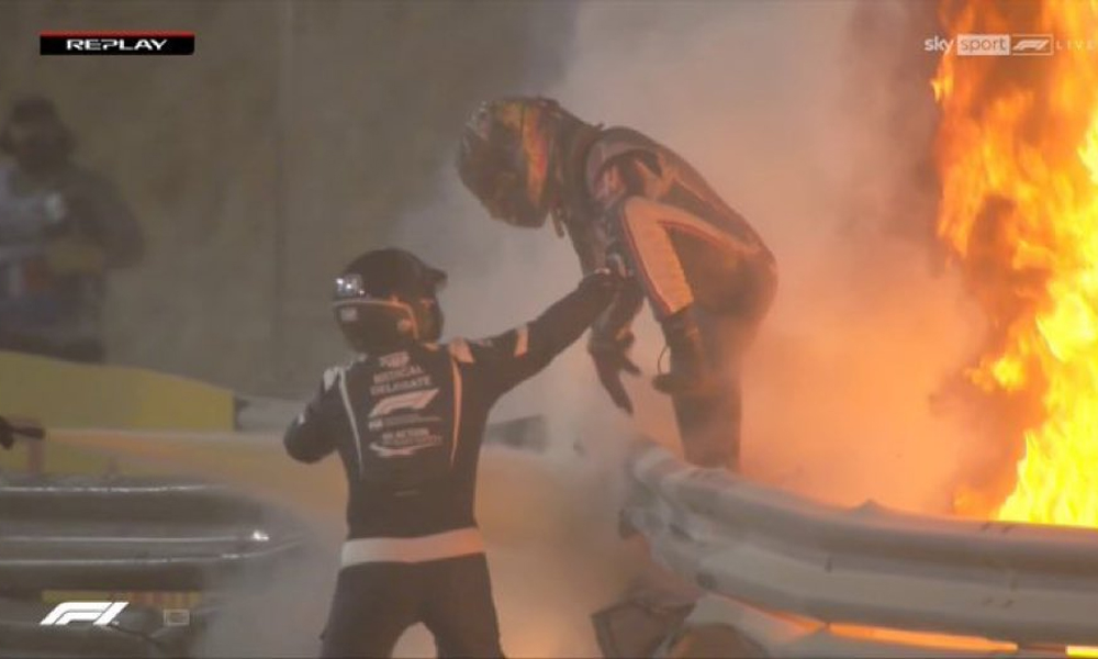 Grosjean (right) stepped out of flames and climbed off the fence, escaping in the horrible crash.  Screen snapshot
