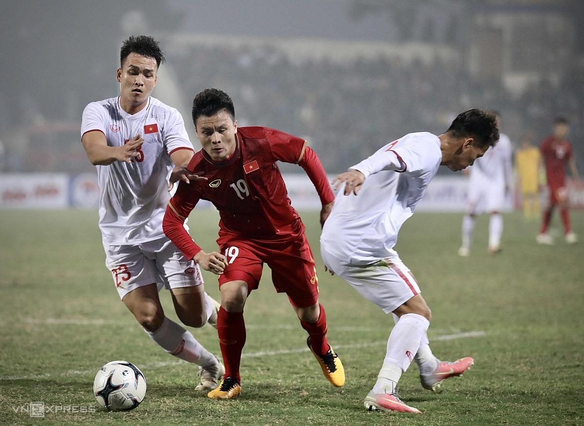 Quang Hải (đỏ) đi bóng qua hai cầu thủ U22 ở trận giao hữu chiều 27/12 trên sân Việt Trì (Phú Thọ). Ảnh: Kim Hoà.