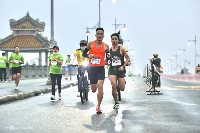 Ha Van Nhat (blue shirt) and Le Quang Hoa (orange shirt) when running across Da Vien bridge.  Photo: VnExpress Marathon.