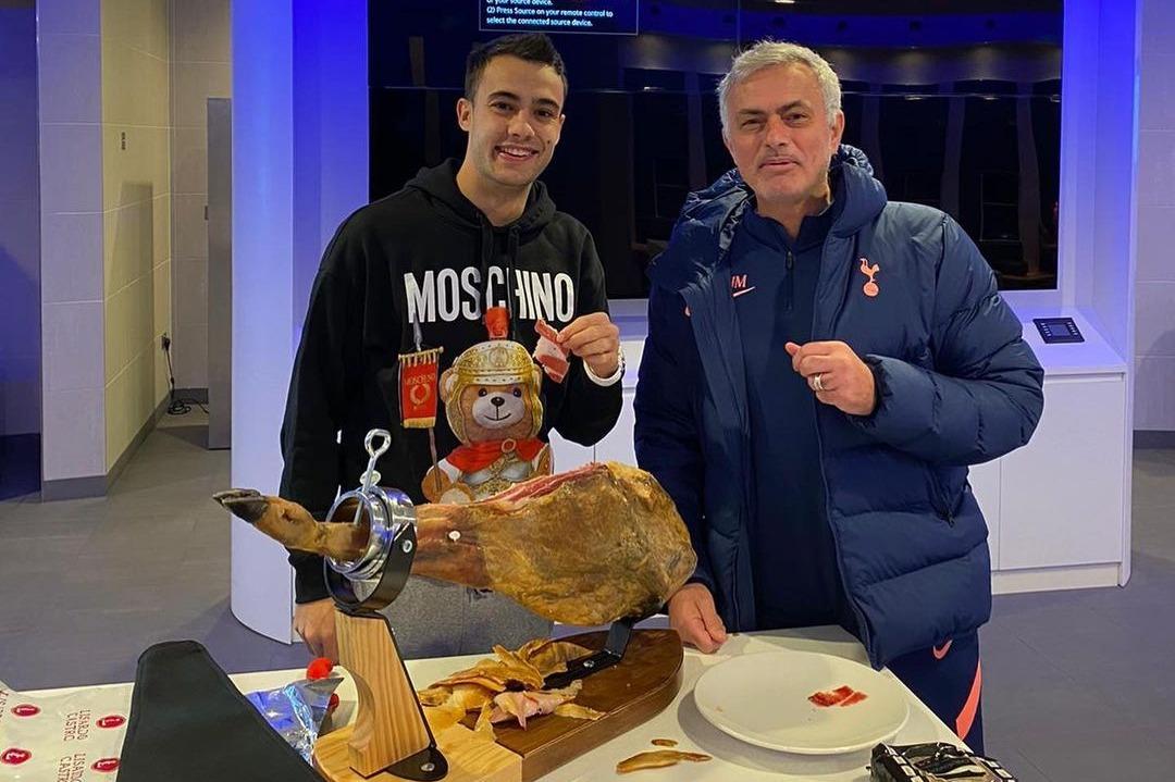 Reguilon (trái) bên cạnh Mourinho khi HLV Tottenham tặng đùi lợn cuối tháng 11. Ảnh: Instagram.