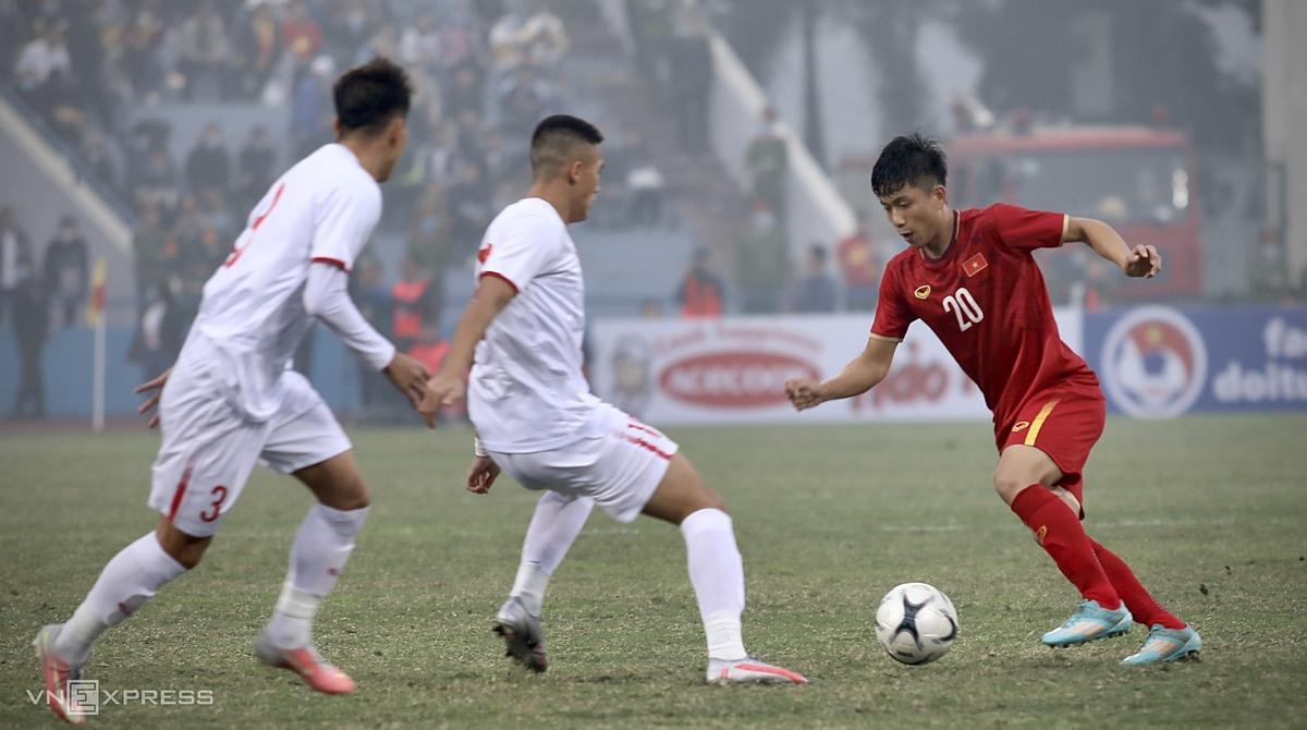 Phan Văn Đức (đỏ) đi bóng trước sự bủa vây của các cầu thủ U22 Việt Nam, trong trận giao hữu trên sân Việt Trì (Phú Thọ) hôm 27/1. Ảnh: Kim Hoà.