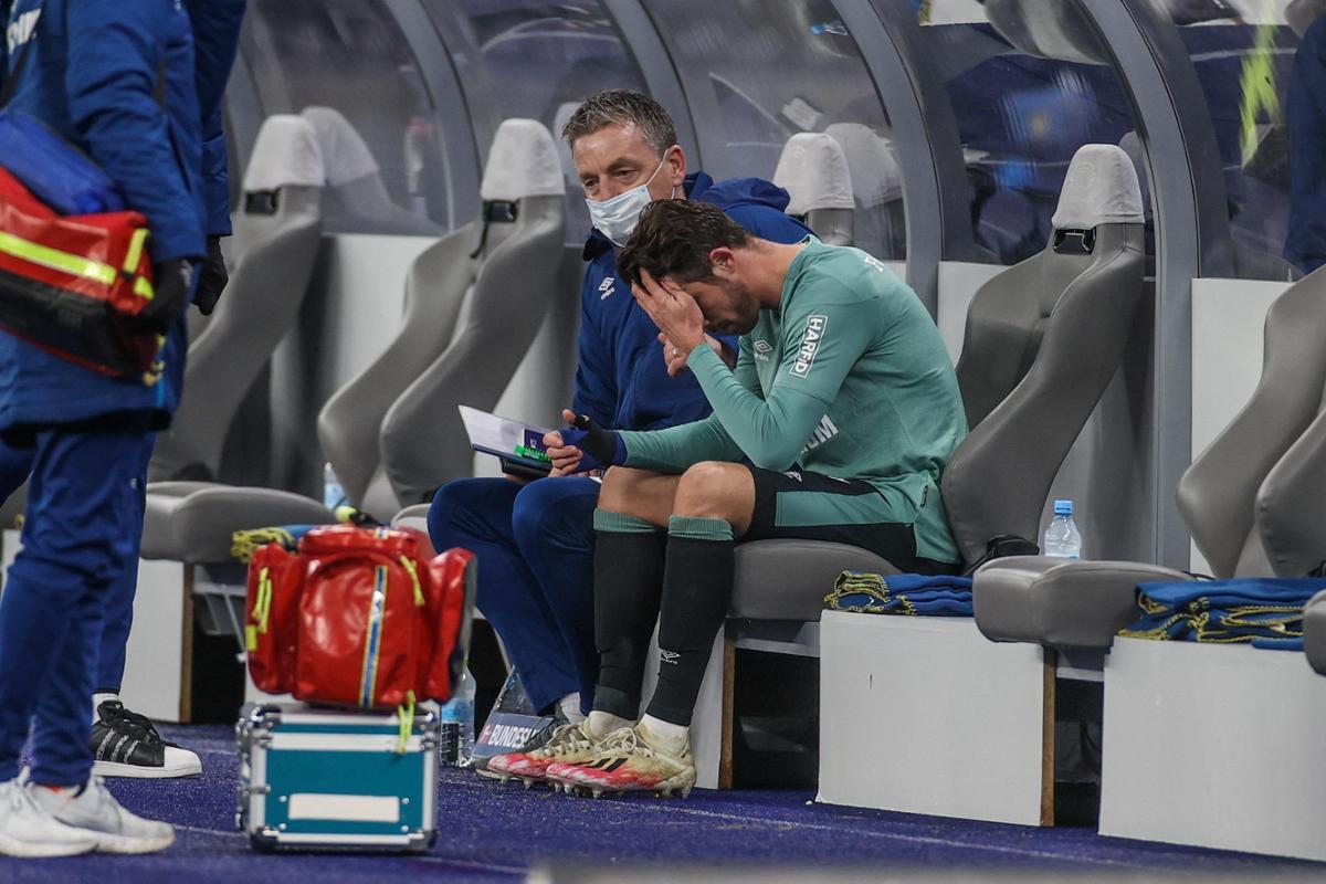 Uth dengan putus asa memeluk wajahnya ketika dia dihibur oleh co-coach Rainer Widmayer setelah kalah dari Hertha pada 2 Januari.  Foto: RHR