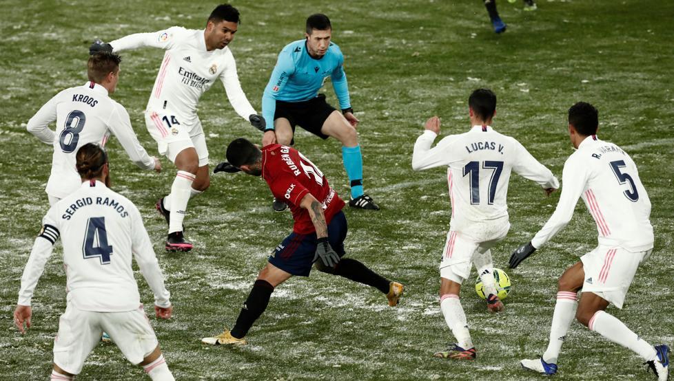 Dù được dọn trước giờ thi đấu, mặt sân El Sadar vẫn phủ nhiều tuyết khi cầu thủ Real và Osasuna so tài. Ảnh: EFE
