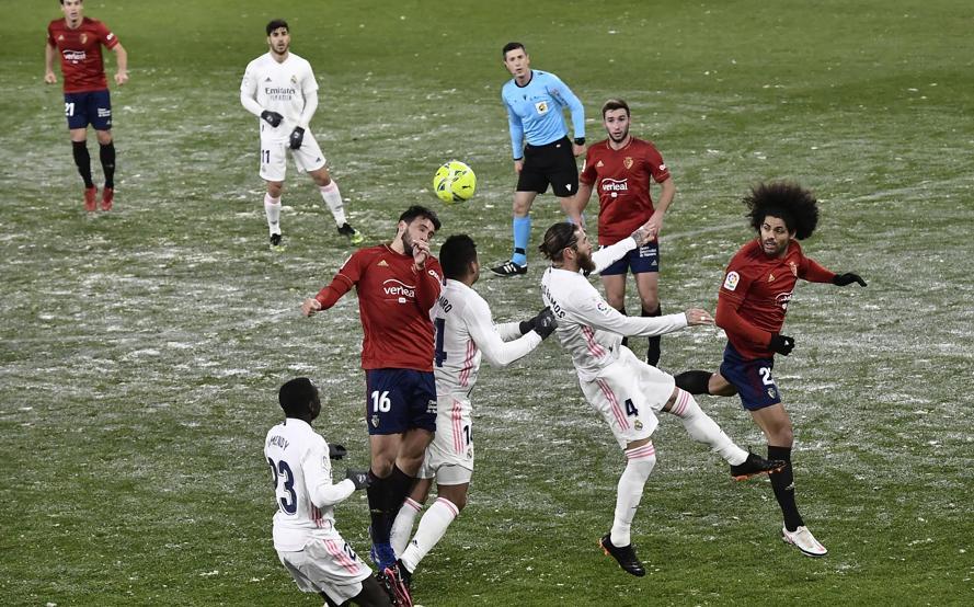 Meski sempat dibersihkan sebelum pertandingan, namun lapangan El Sadar masih tertutup salju saat para pemain Real dan Osasuna bertanding.  Foto: AP