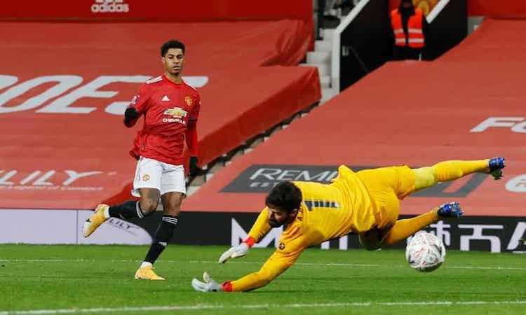 Alisson chạm tay vào bóng nhưng không thể cản cú dứt điểm của Rashford. Ảnh: Reuters.
