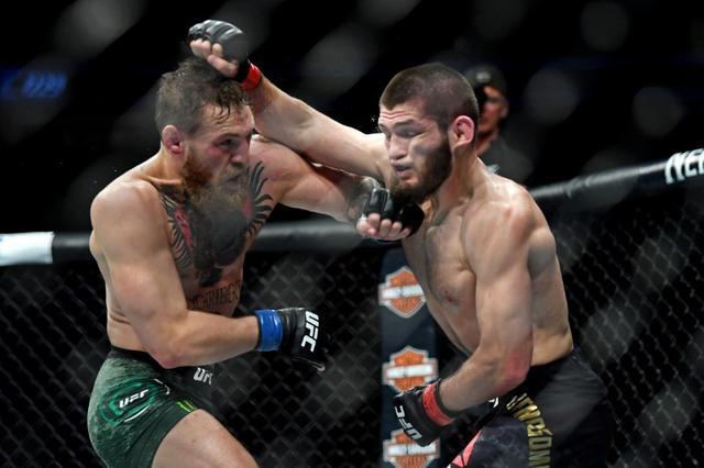 McGregor (trái) từng đập tay xin thua, sau khi bị Khabib siết cổ. Ảnh: Reuters.