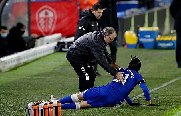 HLV Bielsa giúp Andre Gomes đứng dậy ngoài đường biên. Ảnh: Camera Sport.