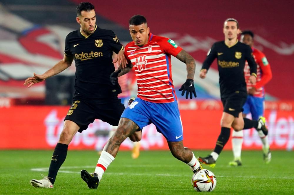Granada (kaos merah) nyaris membuat Barca putus asa dengan dua gol unggulan.  Foto: AP.