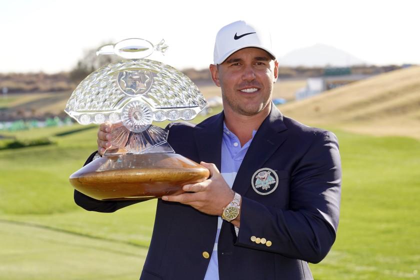 Koepka mengangkat trofi kepada juara Phoenix Open 2021. Foto: AP