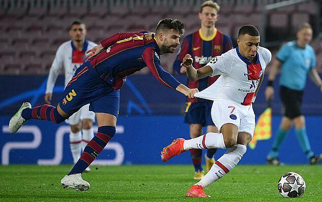 Pique kéo áo Mbappe trong trận đấu trên sân Camp Nou tối 16/2. Ảnh: AFP.