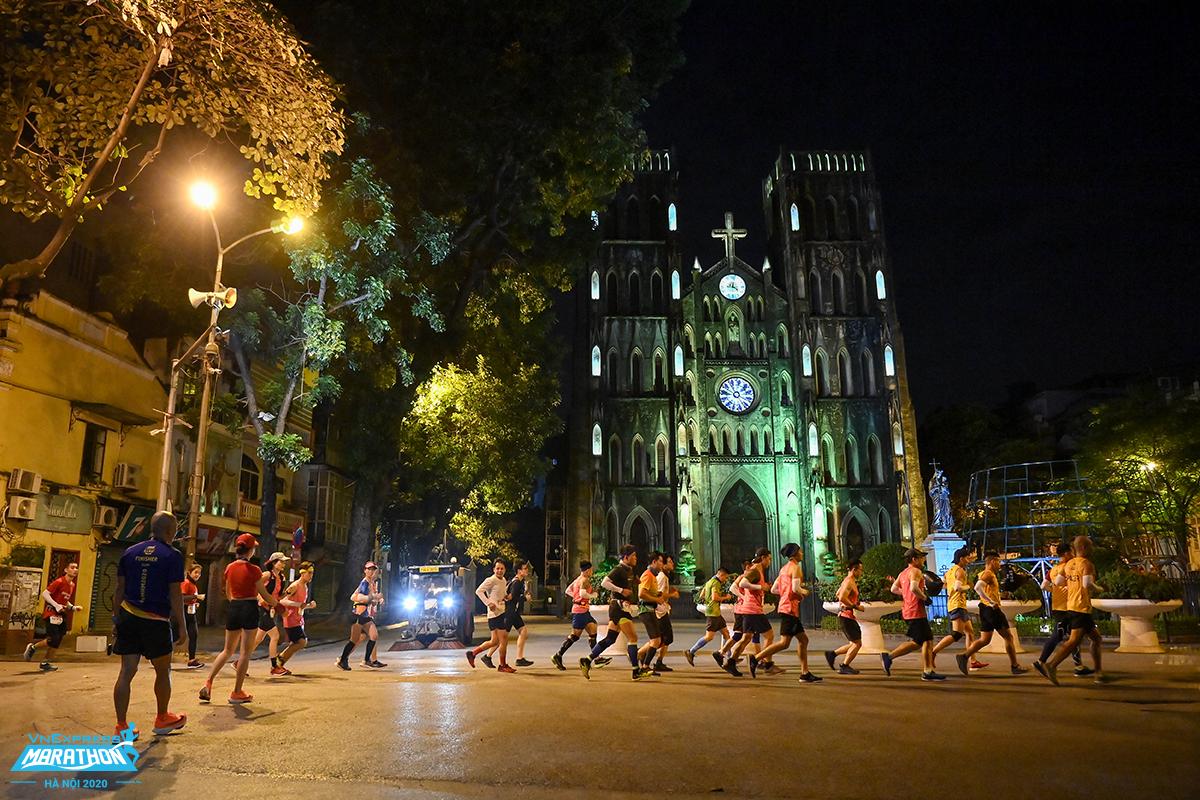 Các vận động viên chạy đêm Hà Nội qua nhà thờ. Ảnh: Hữu Khoa.