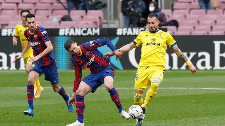 Lenglet (giữa) nỗ lực ngăn chặn pha xuống bóng của cầu thủ Cadiz. Ảnh: Reuters.