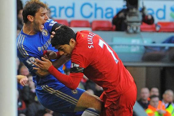 Suarez (phải) cắn tay Ivanovic hôm 21/4/2013 và bị cấm thi đấu 10 trận. Sau đó, tại World Cup 2014, anh tiếp tục cắn Chiellini và bị cấm thi đấu bốn tháng. Ảnh: AFP.