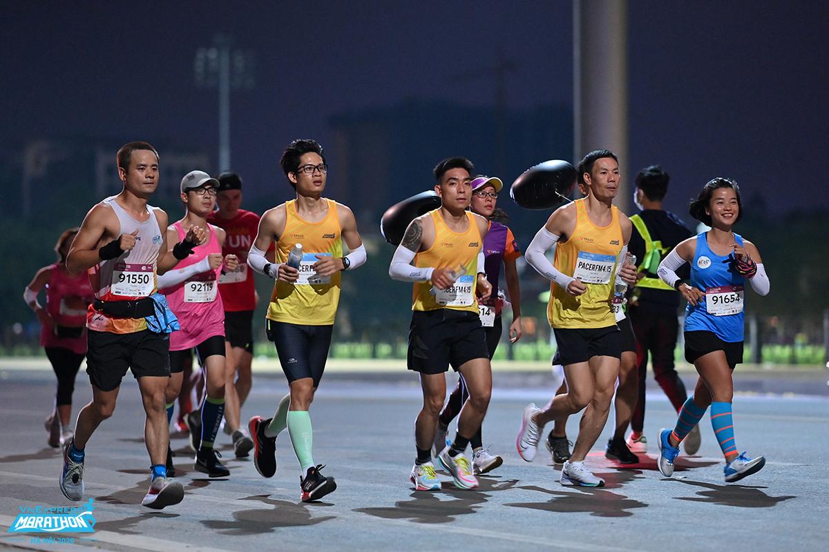 Pacer (yellow shirt) runs with the 42 km athletes in Hanoi night.  Photo: Huu Khoa.