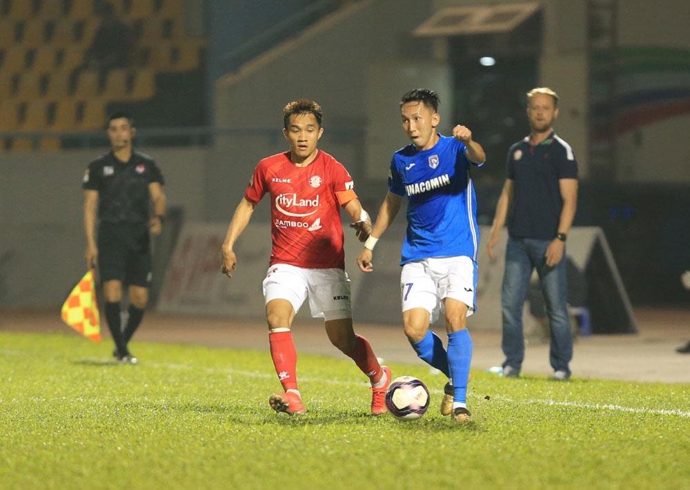 Nghiem Xuan Tu (kaos hijau) melewati pemain Ho Chi Minh City di putaran ketiga V-League 2021 pada 14 Maret.  Foto: VPF.