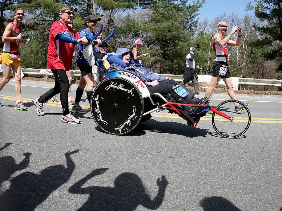 Atlet dan penggemar bertepuk tangan untuk Dick dan Rick selama lari Marathon Boston 2014 terakhir kali.
