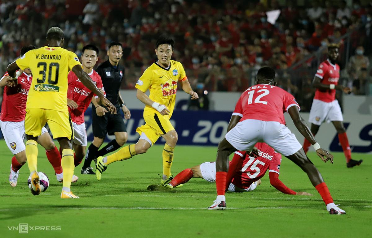 Ha Tinh (kaos merah) bermain bertahan dalam jumlah besar untuk mencegah penyerang HAGL seperti Xuan Truong dan Brandao.  Foto: Duc Hung