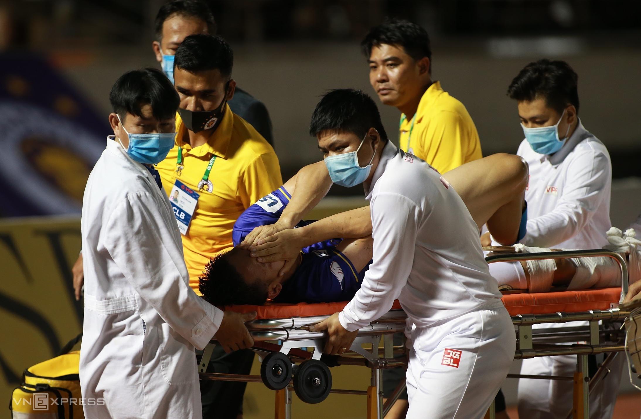 Chân phải của Hùng Dũng được nẹp và băng kín ngay trên sân, trước khi chuyển đến bệnh viện. Ảnh: Lâm Thỏa.