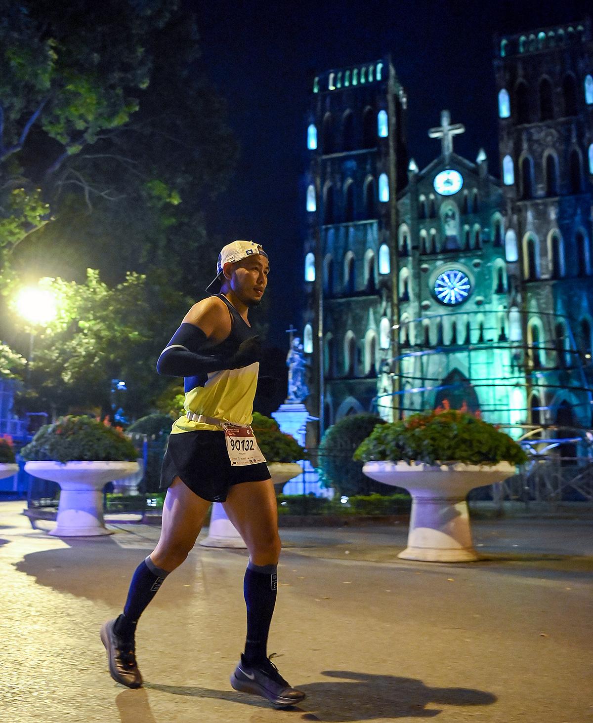 Vận động viên chạy đêm qua Nhà thờ Hà Nội. Ảnh: Hữu Khoa.