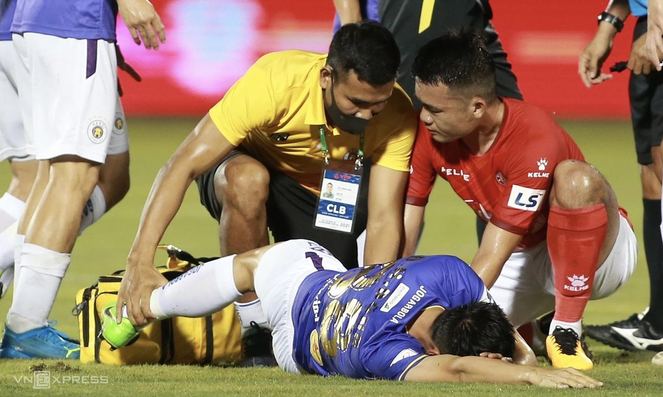 Hoang Thinh mendukung dokter untuk memperbaiki kaki Hung Dung setelah bola, menyebabkan gelandang Hanoi itu patah kakinya.  Foto: Lam Thoa