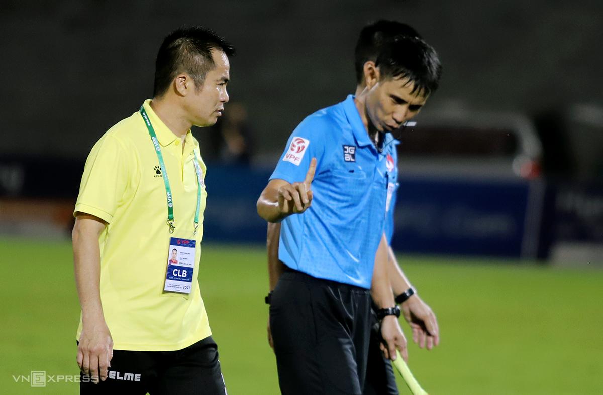 HLV trưởng Hà Tĩnh, ông Phạm Minh Đức (áo vàng) phàn nàn với trọng tài vì không thổi còi sớm. Ảnh: Đức Hùng