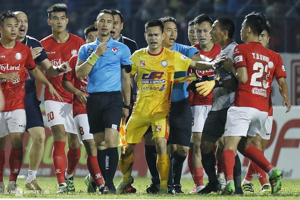 Thủ môn Thanh Thắng (áo xám) phản ứng với trợ lý trọng tài Nguyên Thành trên sân Thanh Hoá ngày 12/4.