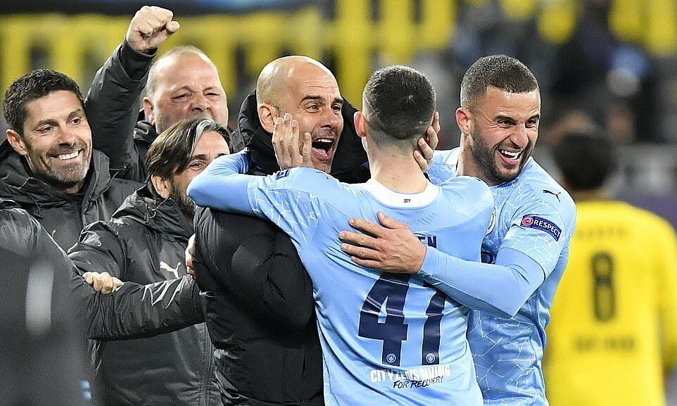 Cầu thủ Man City ôm Guardiola sau khi giành suất vào bán kết Champions League. Ảnh: PA