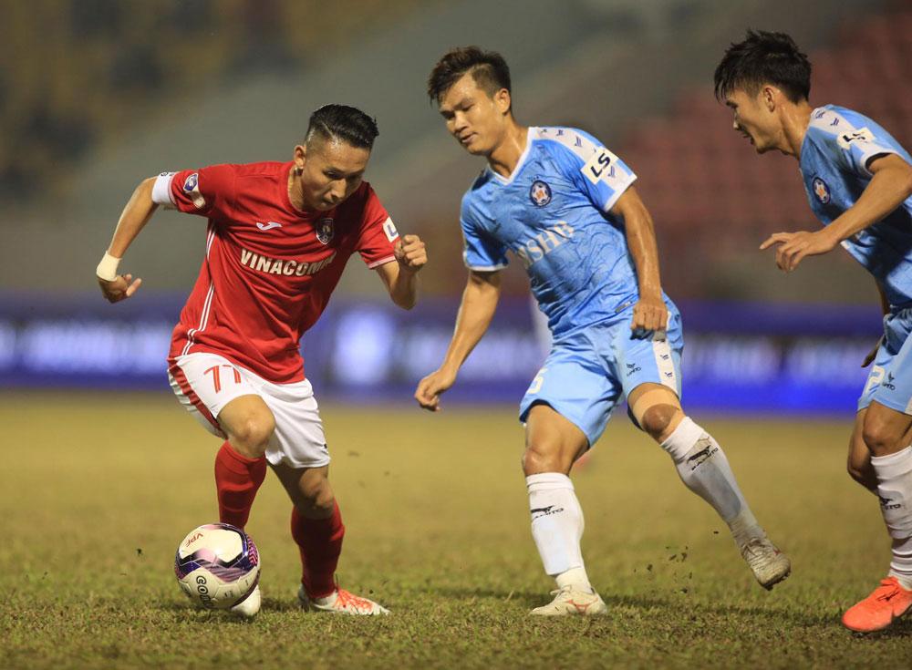 Nghiêm Xuân Tú (trái) đi bóng trong sự truy cản của các cầu thủ Đà Nẵng, ở vòng 2 V-League 2021 trên sân Cẩm Phả. Ảnh: VPF.