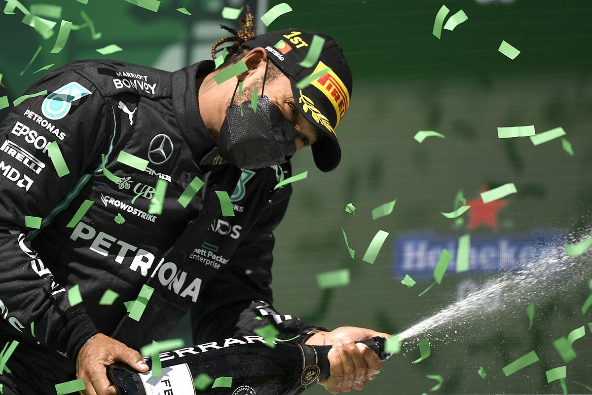 Hamilton merayakan di Podium setelah memenangkan perlombaan Portugis.  Foto: Reuters.