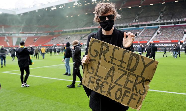 Một CĐV Man Utd giơ khẩu hiệu đòi nhà Glazer cuốn gói khỏi Man Utd. Ảnh: Reuters.