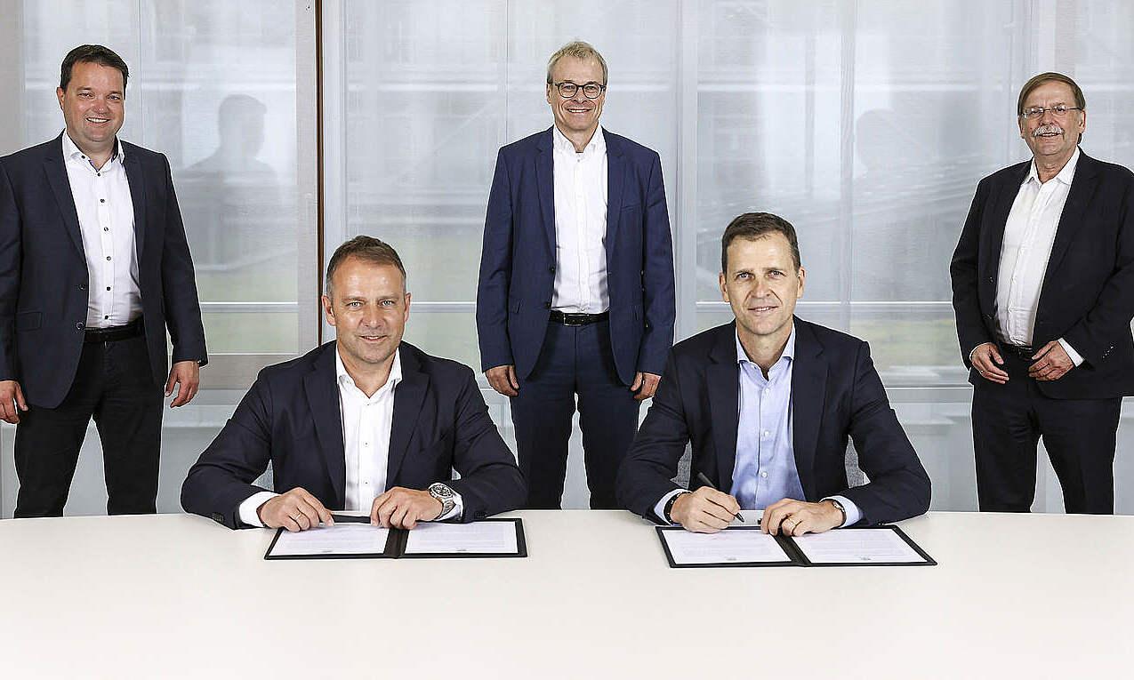 Hansi Flick (trái, hàng ngồi) trong lễ ký hợp đồng với DFB trưa 25/5. Ảnh: DFB