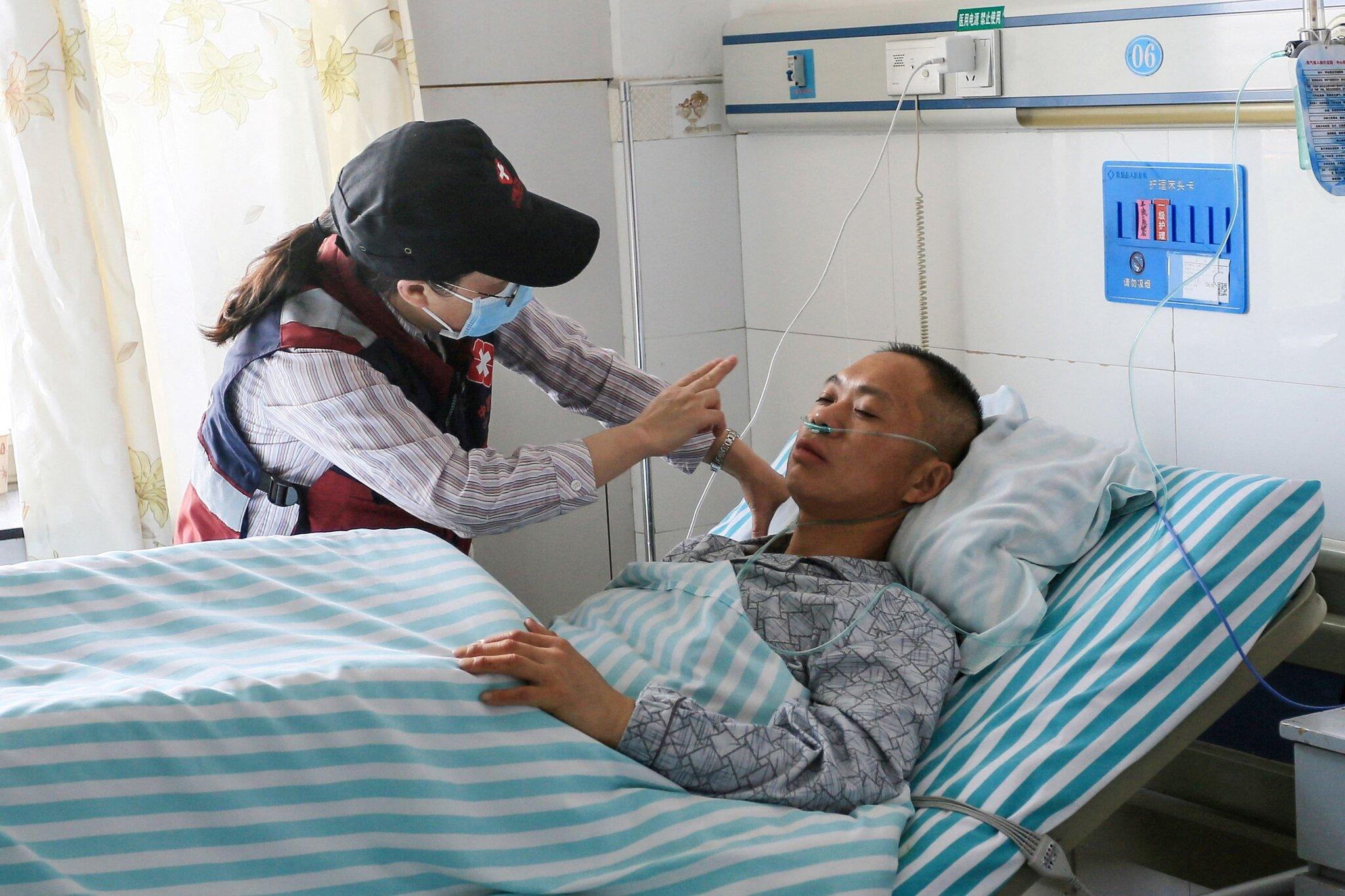 Nhân viên y tế chăm sóc một VĐV được giải cứu từ thảm kịch ở giải chạy tại Cam Túc. Ảnh: AFP