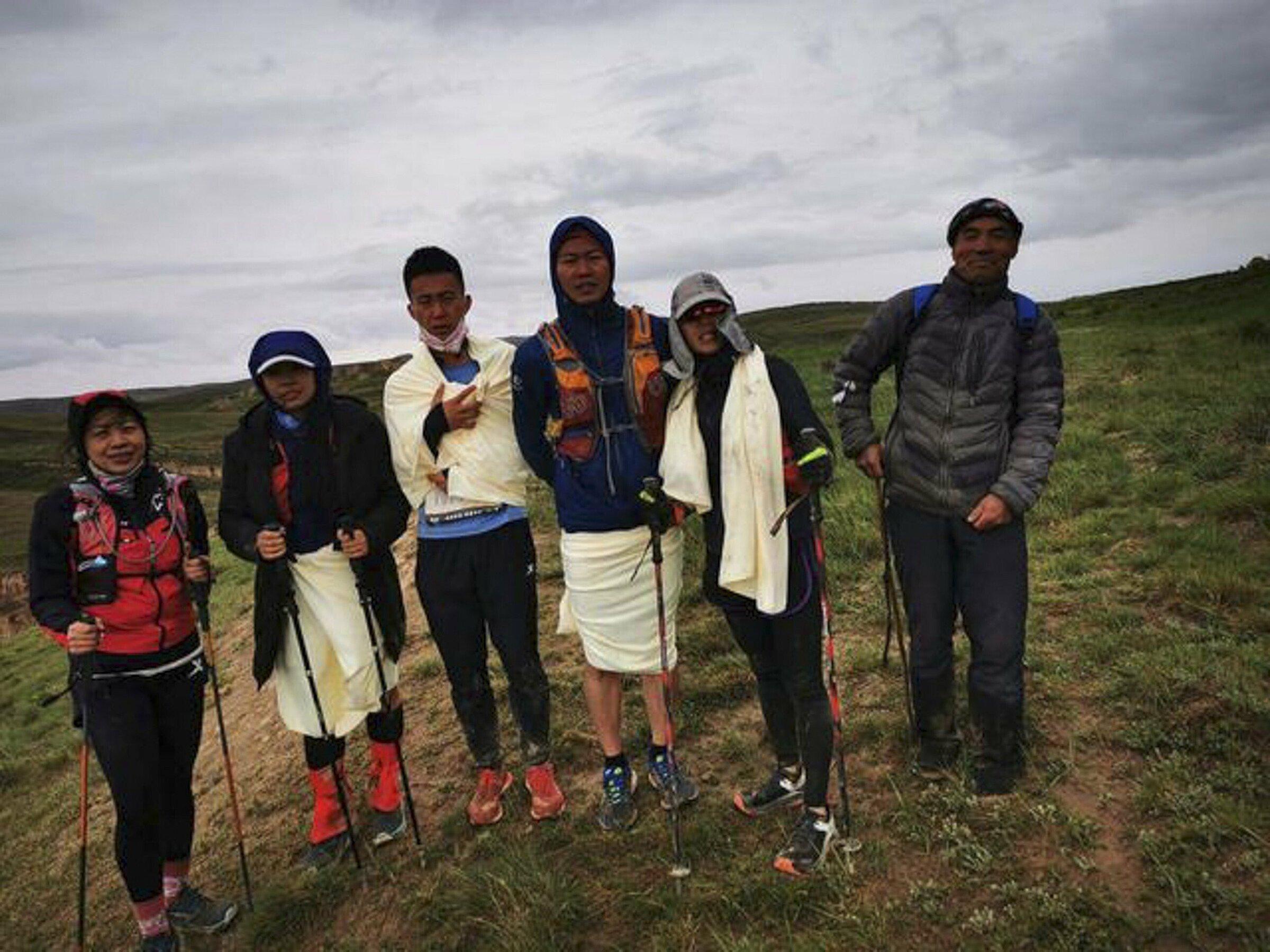 Năm VĐV được giải cứu chụp ảnh lưu niệm vói ân nhân - người chăn cừu Zhu Keming. Ảnh: Handout