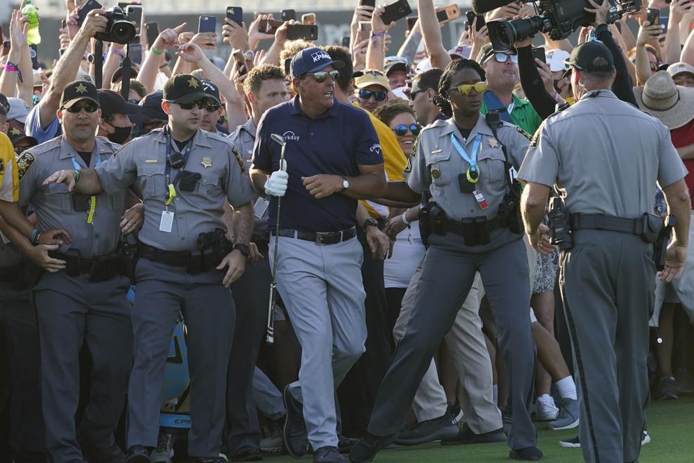Phil Mickelson được lực lượng an ninh hộ tống khi đám đông tràn vào fairway sau cú gạt chốt hố 18. Ảnh: AP