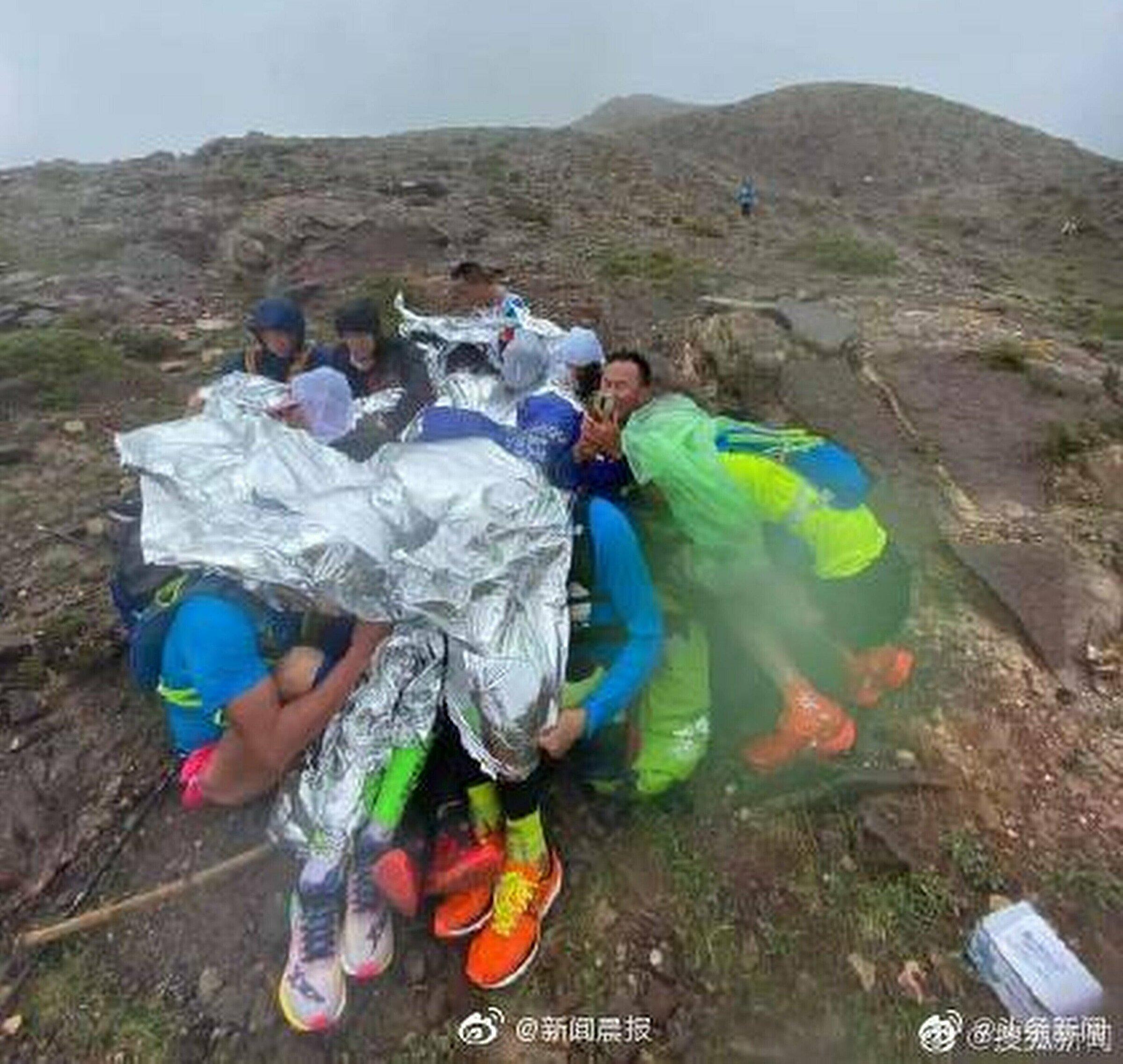 Một nhóm VĐV co cụm trên sườn núi để chống chọi gió giật và mưa lạnh trong lúc chờ giải cứu. Ảnh: news.qq.com