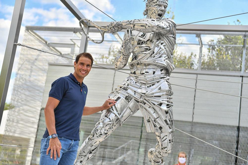 Nadal bên bức tượng mô phỏng cú thuận tay, bên ngoài tổ hợp quần vợt Roland Garros. Ảnh: ATP.