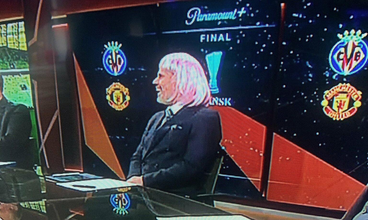 Carragher với mái tóc giả màu hồng trong buổi bình luận chung kết Europa League hôm 26/5.