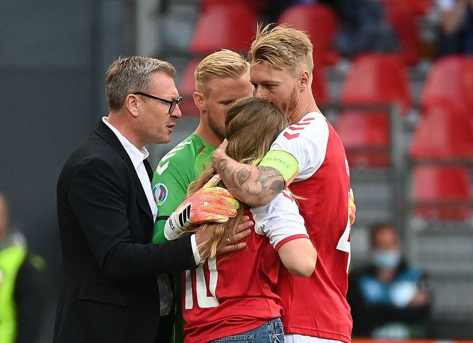 Đội trưởng Kjaer (phải) cùng thủ môn Schmeichel động viên vợ Eriksen. Ảnh: AFP