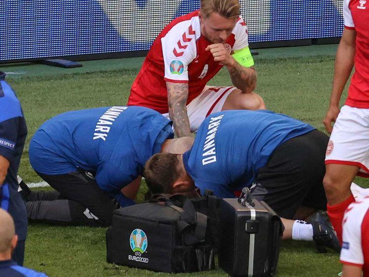Boesen (áo xanh, trái) trong lúc hồi sức tim cho Eriksen trên sân Parken. Ảnh: AFP