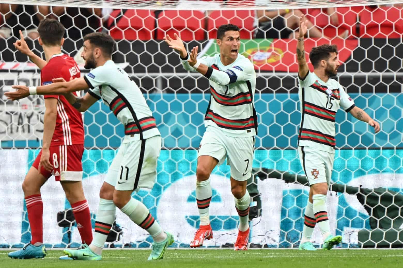 Ronaldo và Bruno Fernandes trong một pha khiếu nại, cho rằng bóng chạm tay cầu thủ Hungary trong vòng cấm đối phương. Ảnh: AFP