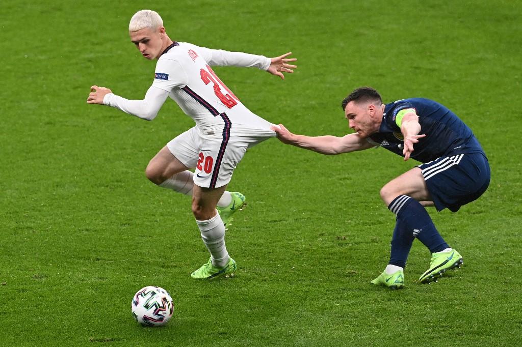 Phil Foden dihentikan oleh pemain Skotlandia.  Foto: AFP.