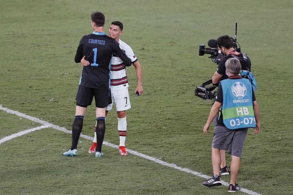 Courtois động viên Ronaldo sau trận đấu ở vòng 1/8. Ảnh: AFP.