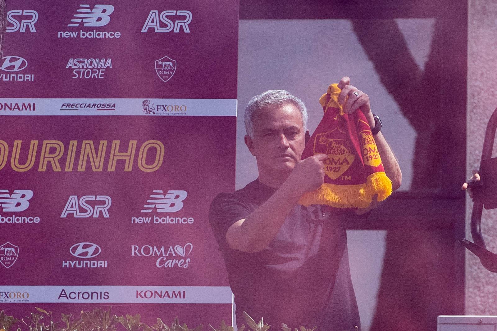 """Mourinho ชี้ไปที่โลโก้ Roma บนผ้าพันคอแบบดั้งเดิมในขณะที่เขาทักทายแฟน ๆ ของทีมใหม่ใน Trigoria ชานเมืองกรุงโรมเมื่อวันที่ 2 กรกฎาคม  ภาพถ่าย: """"AS Roma ."""""""