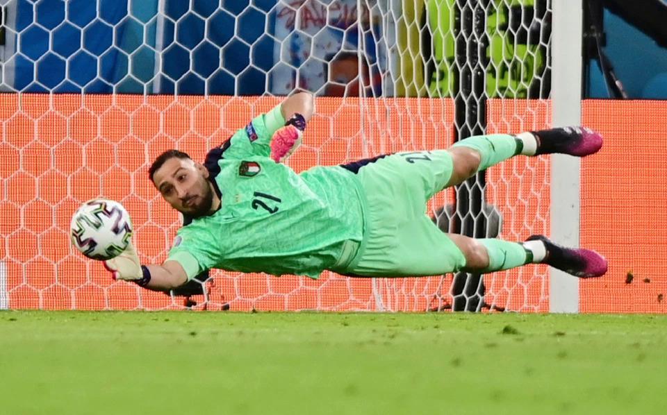 Donnarumma bay người đẩy cú sút chéo góc của Lukaku ở hiệp một trận tứ kết Bỉ - Italy. Ảnh: AP