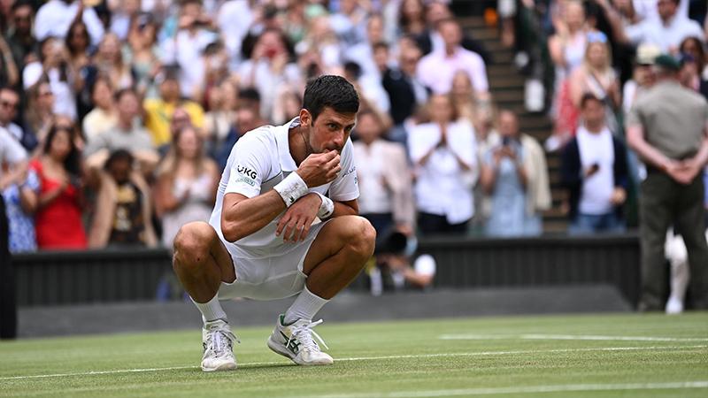Djokovic mengulangi aksi makan rumputnya setelah memenangi Wimbledon untuk ketiga kalinya secara beruntun.  Foto: Wimbledon