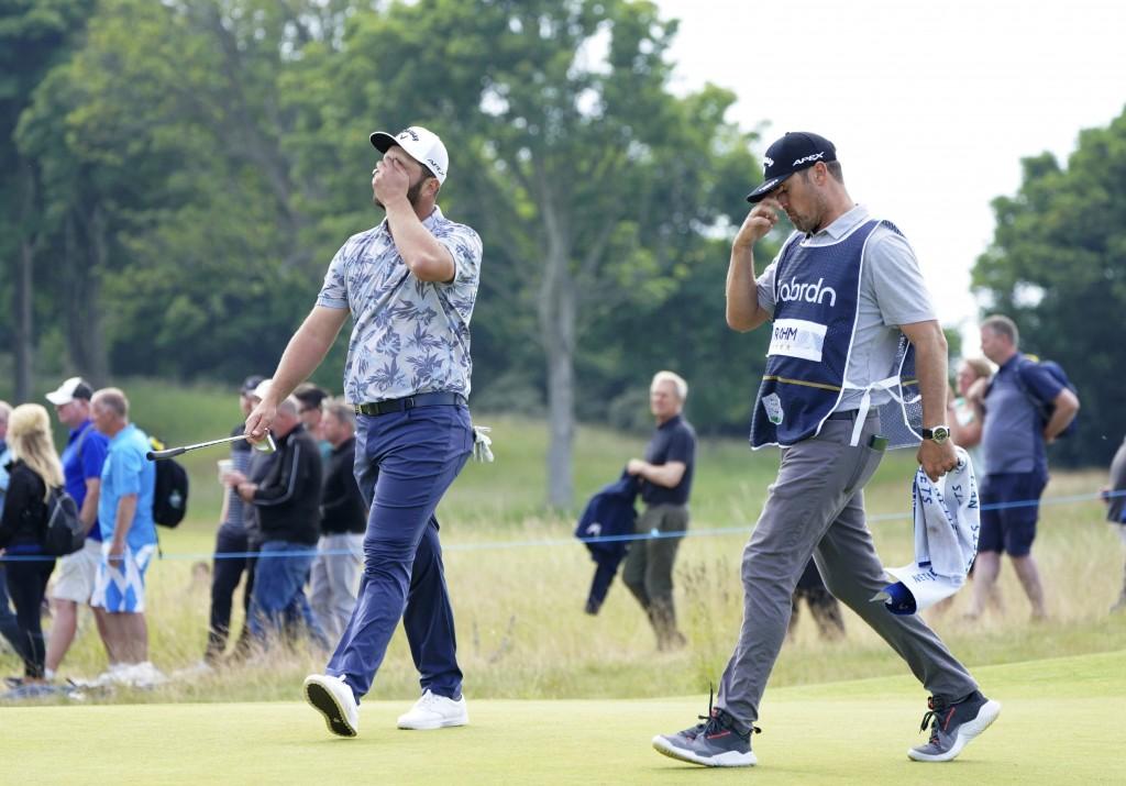 Rahm (kiri) membelai wajahnya saat meninggalkan green ronde ketiga hole 16 Scottish Open pada 11 Juli.  Foto: AP