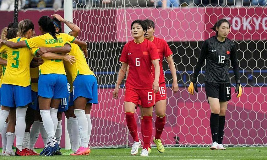 Trung Quốc (áo đỏ) thua đậm Brazil nhưng vẫn còn nhiều cơ hội đi tiếp. Ảnh: AP