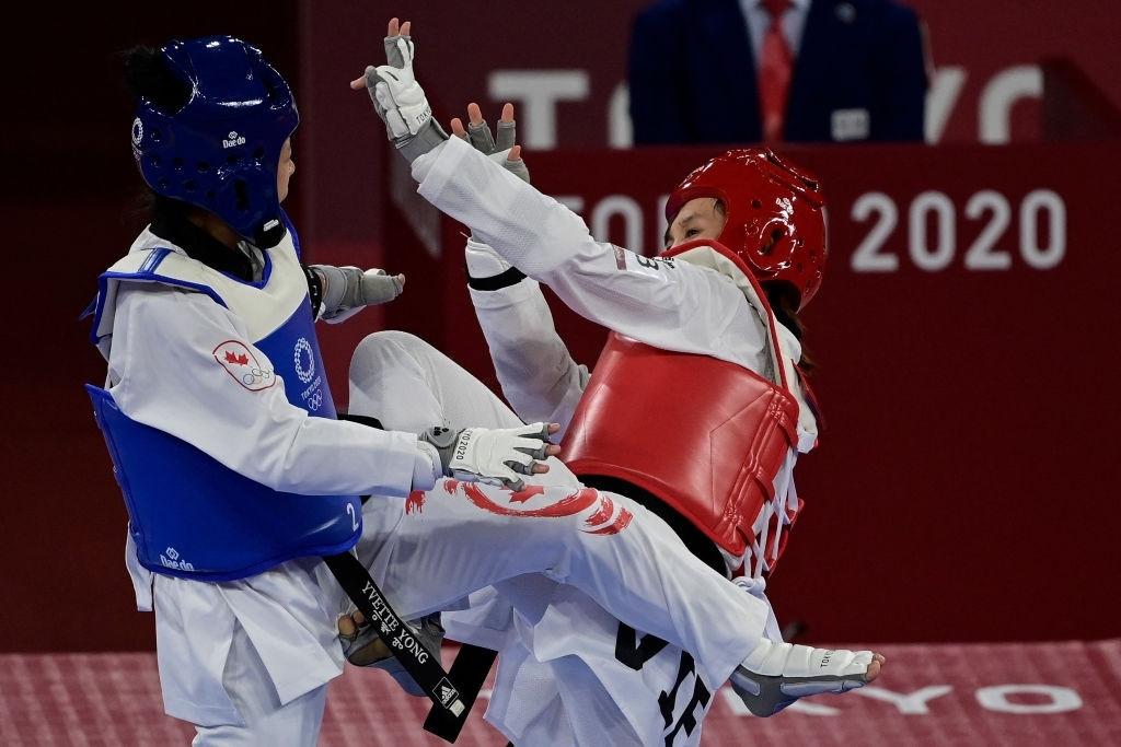Kim Tuyen (tombak merah - topi merah) dalam fase dekat untuk menghindari serangan Yvette Yong.  foto: AFP