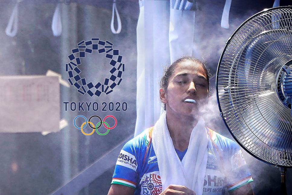 Một cua-rơ nữ kiệt sức, phải dùng quạt nước thổi vào người sau khi xong phần thi ở Olympic 2020. Ảnh: AFP