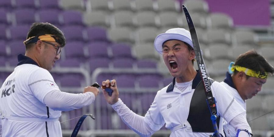 Je Deok (giữa) giành huy chương vàng đồng đội nam cùng Woo Jin và Jin Hyek. Ảnh: AP.